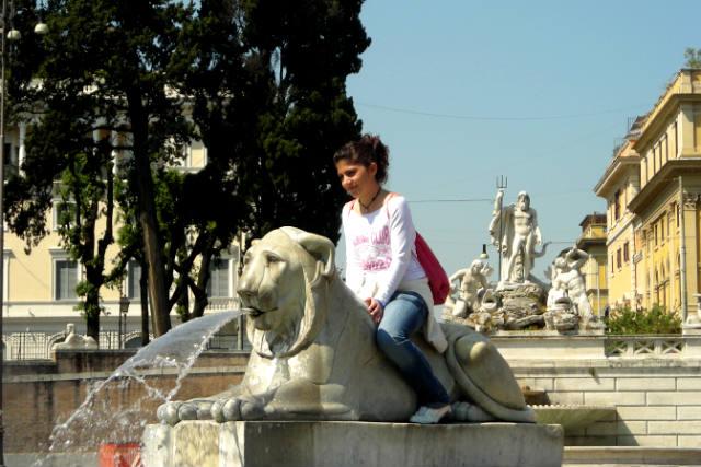 Turista subida a los leones de la fuente de Piazza del Popolo - Destino y Sabor